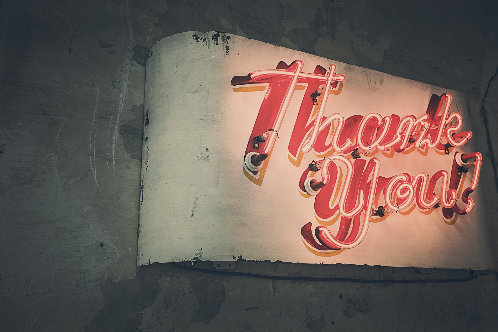A unique, vintage red thank you typography plexiglass sign used in a business or restaurant as a promotional tool.