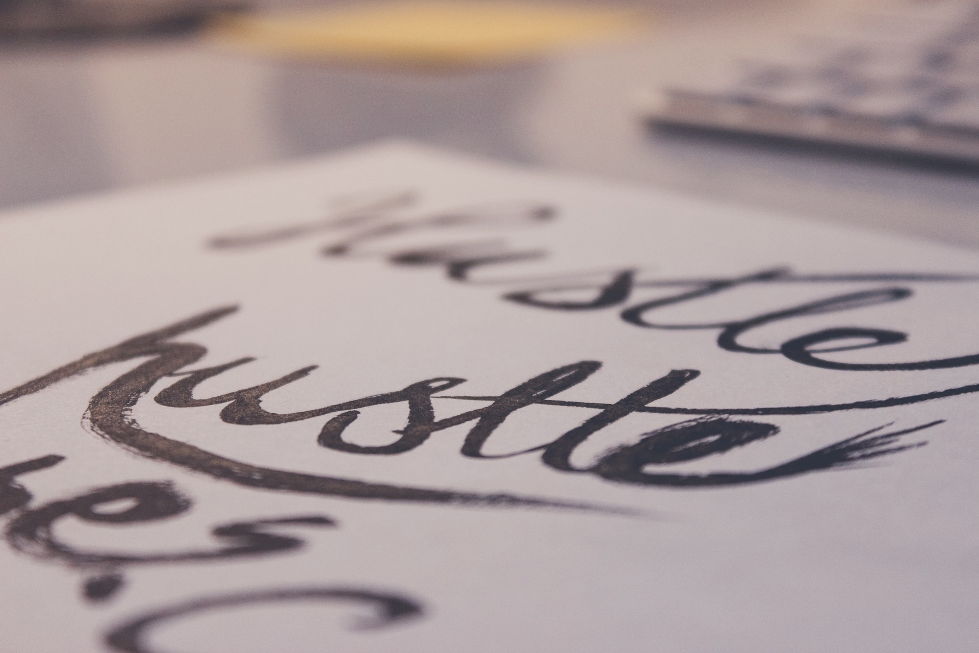 A sheet of paper with a handwritten typography made by a calligraphy pen with the word hustle.