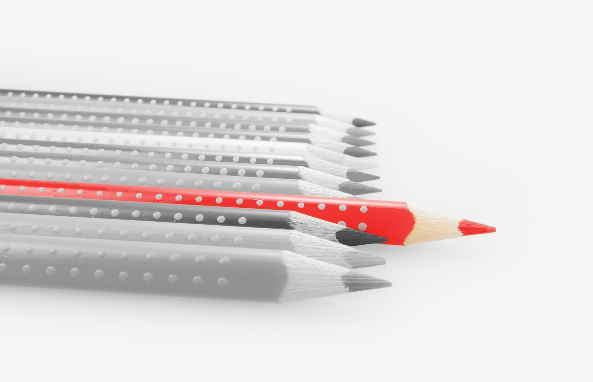In a black and white image of pencils, with one unique and creative one that stands out from the rest.